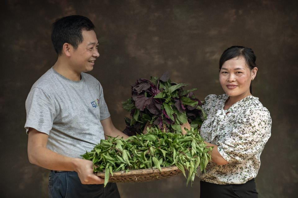 A man and a woman carrying vegetables